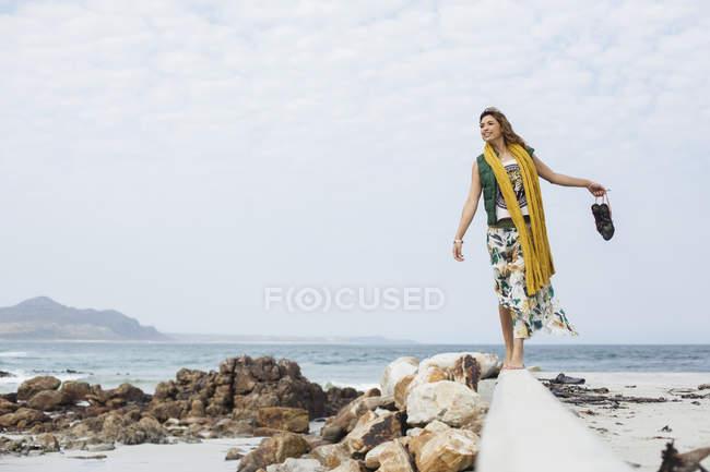 Junge Frau zu Fuß auf Betonklotz am Strand, Kapstadt, Westkap, Südafrika — Stockfoto