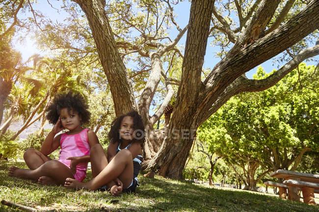 Retrato de duas jovens irmãs, sentadas ao lado da árvore — Fotografia de Stock