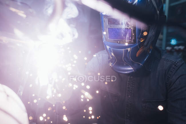 Mature man in garage, working on motorcycle, using welding equipment — Stock Photo
