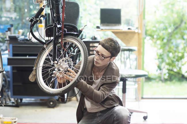 Жінка в майстерню з ремонту велосипедів ремонту колесо на лежачому велосипеді — стокове фото