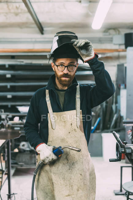 Portrait of metalworker holding welding torch in forge workshop — Stock Photo