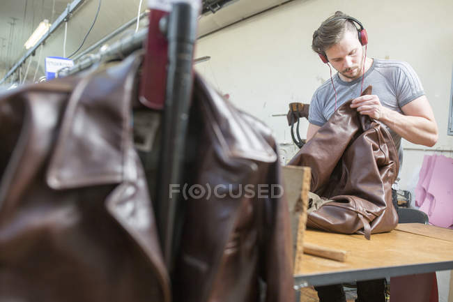 Man working in leather jacket manufacturers — Stock Photo