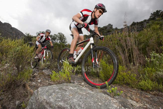 Молодая пара катается на горных велосипедах по грунтовой дорожке — стоковое фото