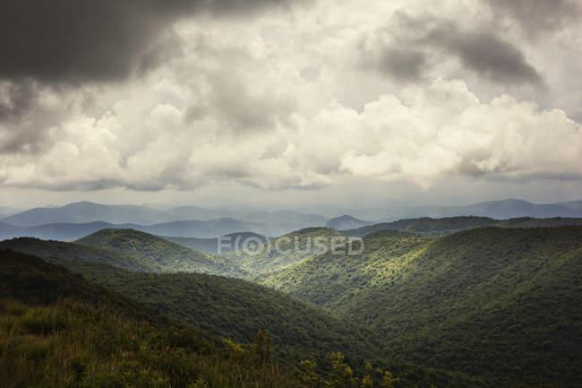 Montagnes vertes couvertes sous un ciel nuageux — Photo de stock