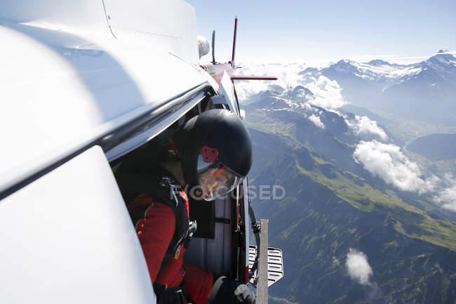 Mergulhador no céu feminino em helicóptero verificando a saída sobre a montanha, Interlaken, Berna, Suíça — Fotografia de Stock