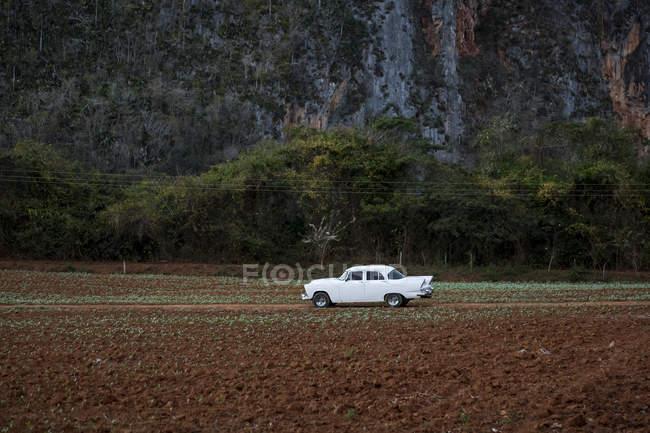 Retro-weißes Auto in ländlichen Landschaft von Berg — Stockfoto