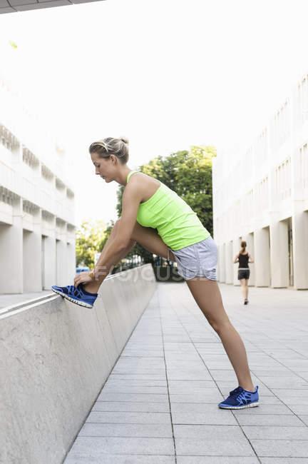 Jovem mulher se alongando no beco entre edifícios de escritórios — Fotografia de Stock