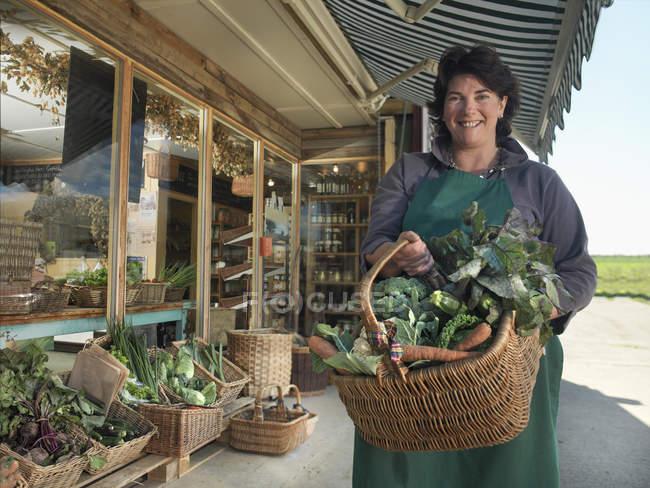 Портрет женщины-органического фермера с корзиной органических овощей за пределами фермерского магазина — стоковое фото