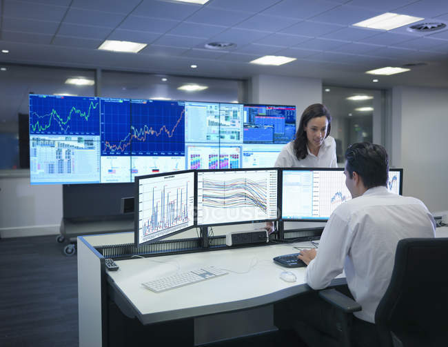 Financial analysts working with graphs on screens in control room — Stock Photo