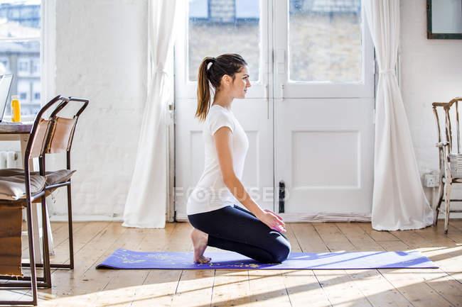 Junge Frau praktizieren Yoga kniende Position in Wohnung — Stockfoto