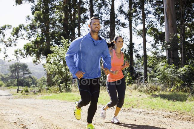 Молодая пара бегает в лесу — стоковое фото
