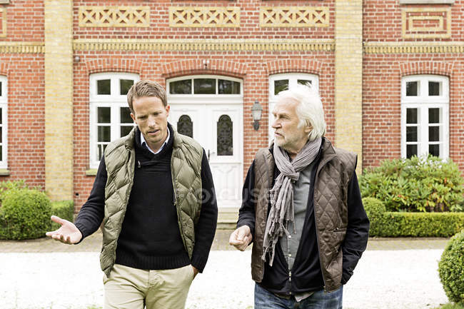 Отец и сын идут перед домом — стоковое фото