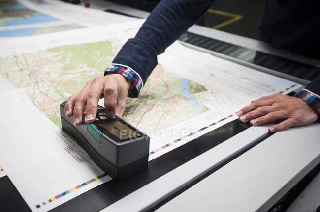 Trabalhador, verificando a qualidade de impressão de produtos na oficina de impressão — Fotografia de Stock