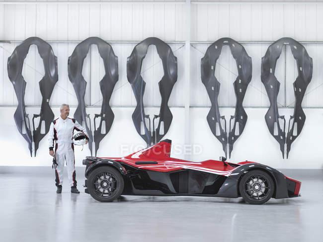 Rennfahrer mit Supersportwagen in Fabrik mit Carbon Fibre Auto Karosserien an Wand — Stockfoto