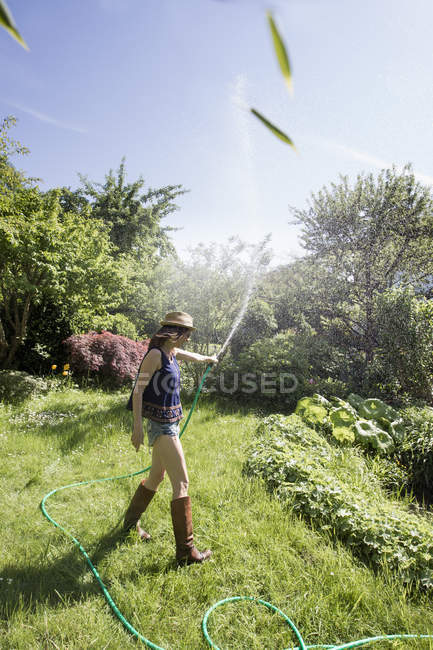 Side view of mature woman in garden squirting water into air with hosepipe — Stock Photo