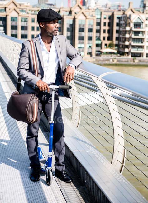Homme d'affaires avec scooter, Millennium Bridge, Londres, Royaume-Uni — Photo de stock
