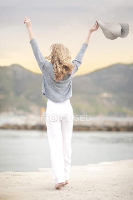 Rückansicht der Frau stretching mit Hut in der Hand, Hout Bay, Kapstadt, Südafrika — Stockfoto