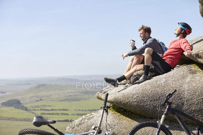 Cyclistes reposant sur l'éperon rocheux — Photo de stock