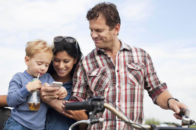Family looking at smartphone and having a drink — Stock Photo