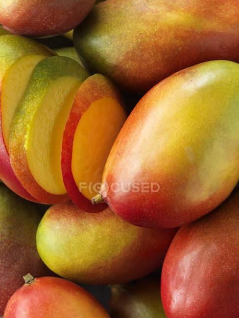 Whole and sliced mangoes, close up shot — Stock Photo