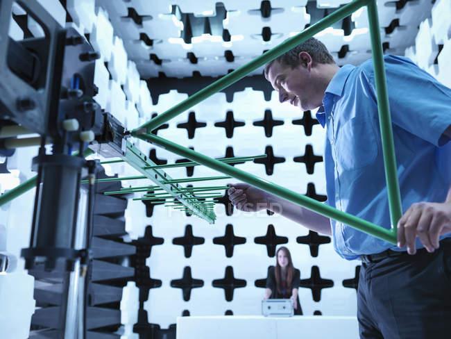 Инженеры проверяют двухлоговую антенну на электромагнитную совместимость (Emc) излучаемых иммунитета тестирования в полуанехотической камере по отношению к электронному оборудованию в тестируемом (Eut) — стоковое фото