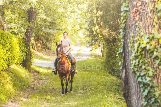 Женщина, скачущая на лошади по дорожке с деревьями, смотрит в камеру — стоковое фото