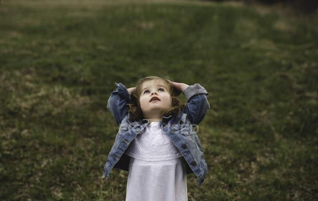Молодая девушка с руками на голове смотрит на луг — стоковое фото
