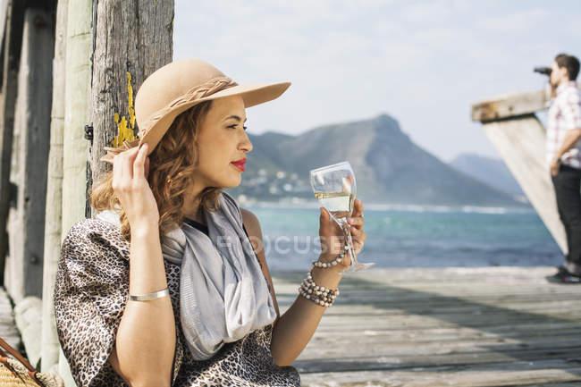 Joven mujer glamorosa bebiendo vino en el muelle costero, Ciudad del Cabo, Cabo Occidental, Sudáfrica - foto de stock