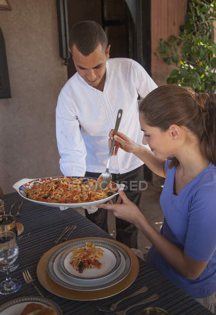 Waiter offering woman food on serving dish, Marrakesh, Morocco — Stock Photo
