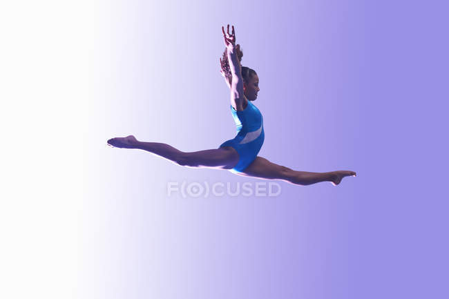 Young gymnast in mid-air leap — Stock Photo