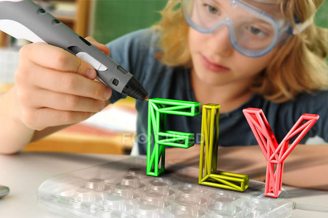 Boy with digital pen and 3D model of capital-lettered word in classroom — Stock Photo