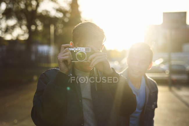 Молодой человек фотографирует на солнечной улице — стоковое фото