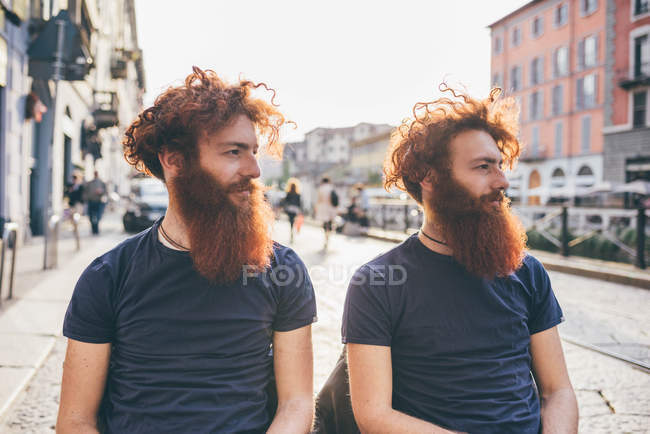Young male hipster twins with red hair and beards on city street — Stock Photo