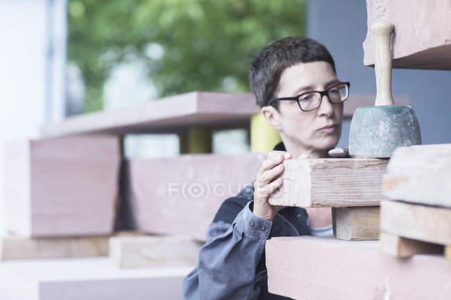 Stonemason quality checking blocks of stone — Stock Photo