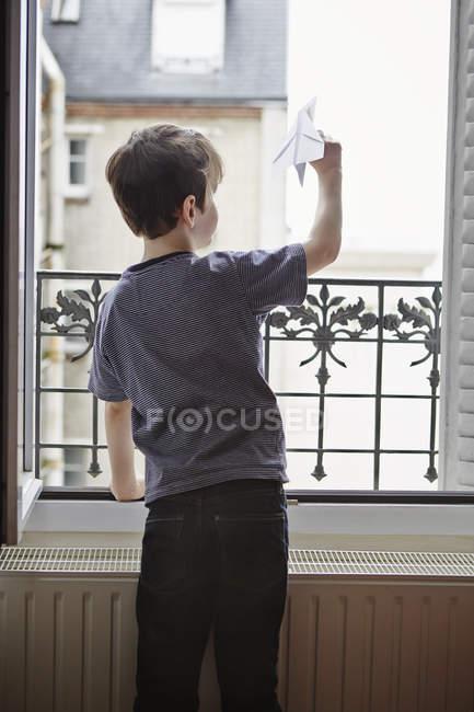 Menino lançando avião de papel da janela, visão traseira — Fotografia de Stock