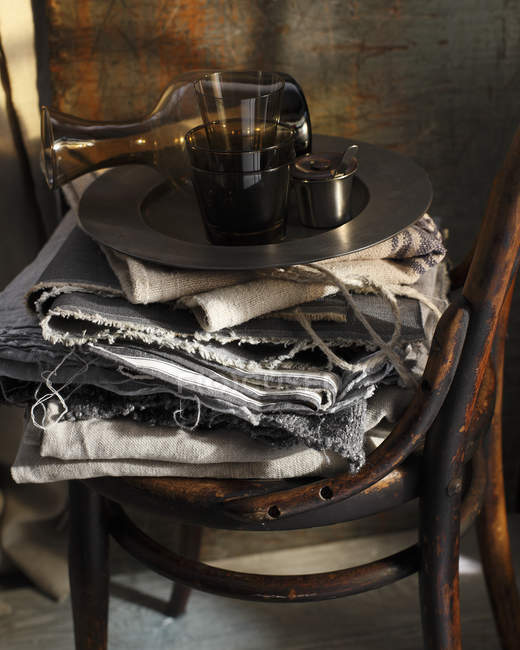 Glasses cups and decanter on textiles and vintage chair — Stock Photo