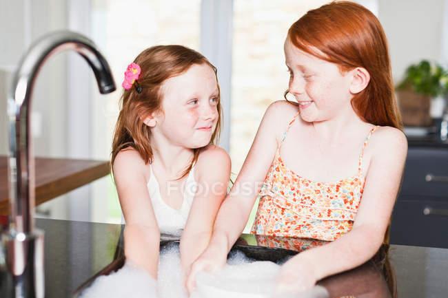 Smiling girls washing dishes in sink — Stock Photo