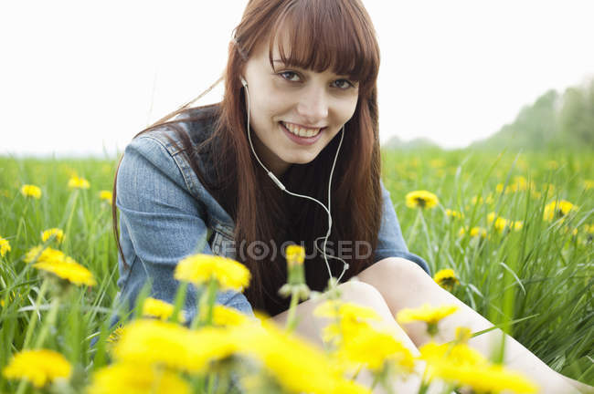 Retrato de mujer joven en auriculares en el campo de los dientes de león - foto de stock