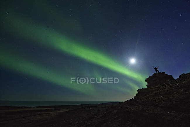 Silhouette of man standing on rocks with raised hands and sky illuminated with Northern Lights — Stock Photo
