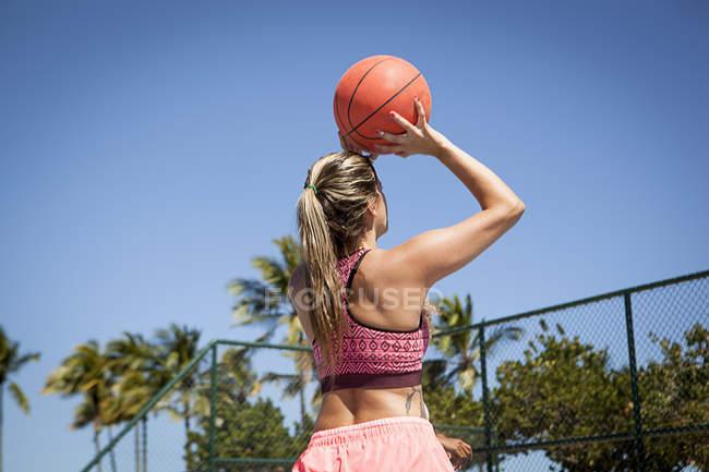 Молодая женщина с баскетболом, вот-вот выстрелит, вид сзади — стоковое фото