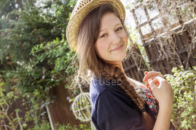 Portrait of teenage girl in straw hat in garden — Stock Photo