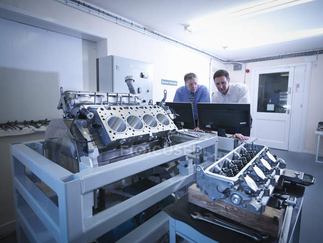 Engineers inspecting automotive engine in test facility — Stock Photo