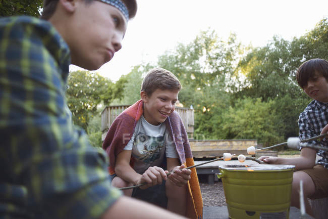 Group of little boys toasting marshmallows over bucket barbecue — Stock Photo