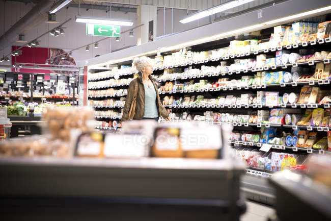 Mature woman looking at grocery shelves in supermarket — Stock Photo