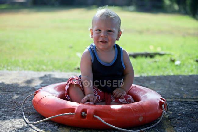 Мальчик сидит в спасательный — стоковое фото