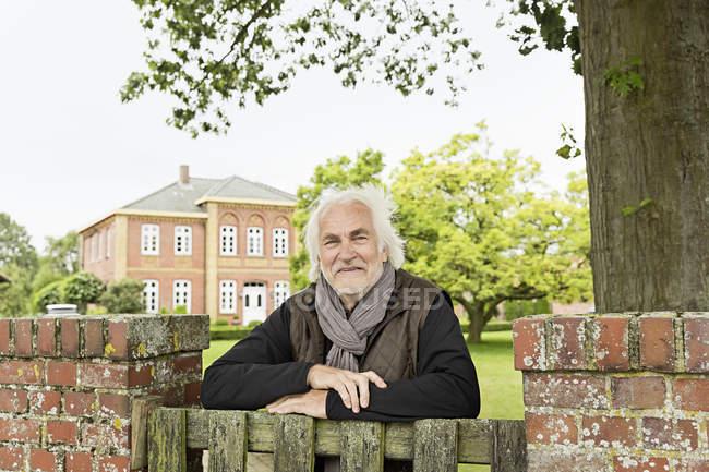 Старший опирается на деревянные ворота — стоковое фото