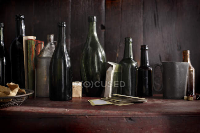 Close up shot of pile of emty wine bottles on wooden table — Stock Photo