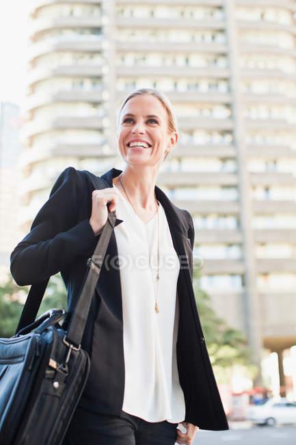 Femme d'affaires portant la mallette à l'extérieur — Photo de stock