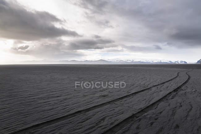 Vestígios de rodas na areia vulcânica preta sob céu nublado — Fotografia de Stock