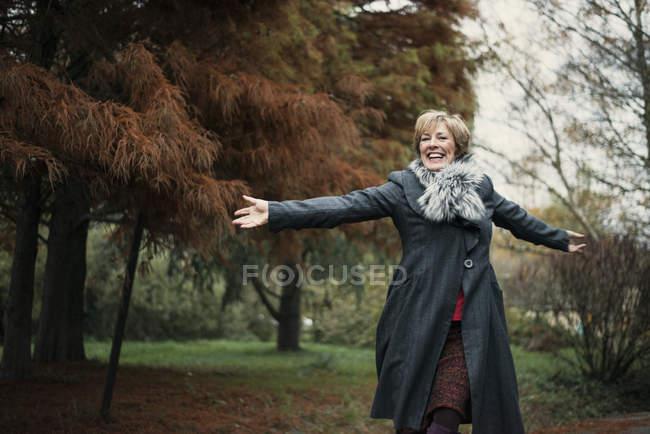 Porträt von Reife Frau, ausgestreckte Arme im freien — Stockfoto